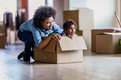 Happy single mother and her small daughter in cardboard box at their new home.